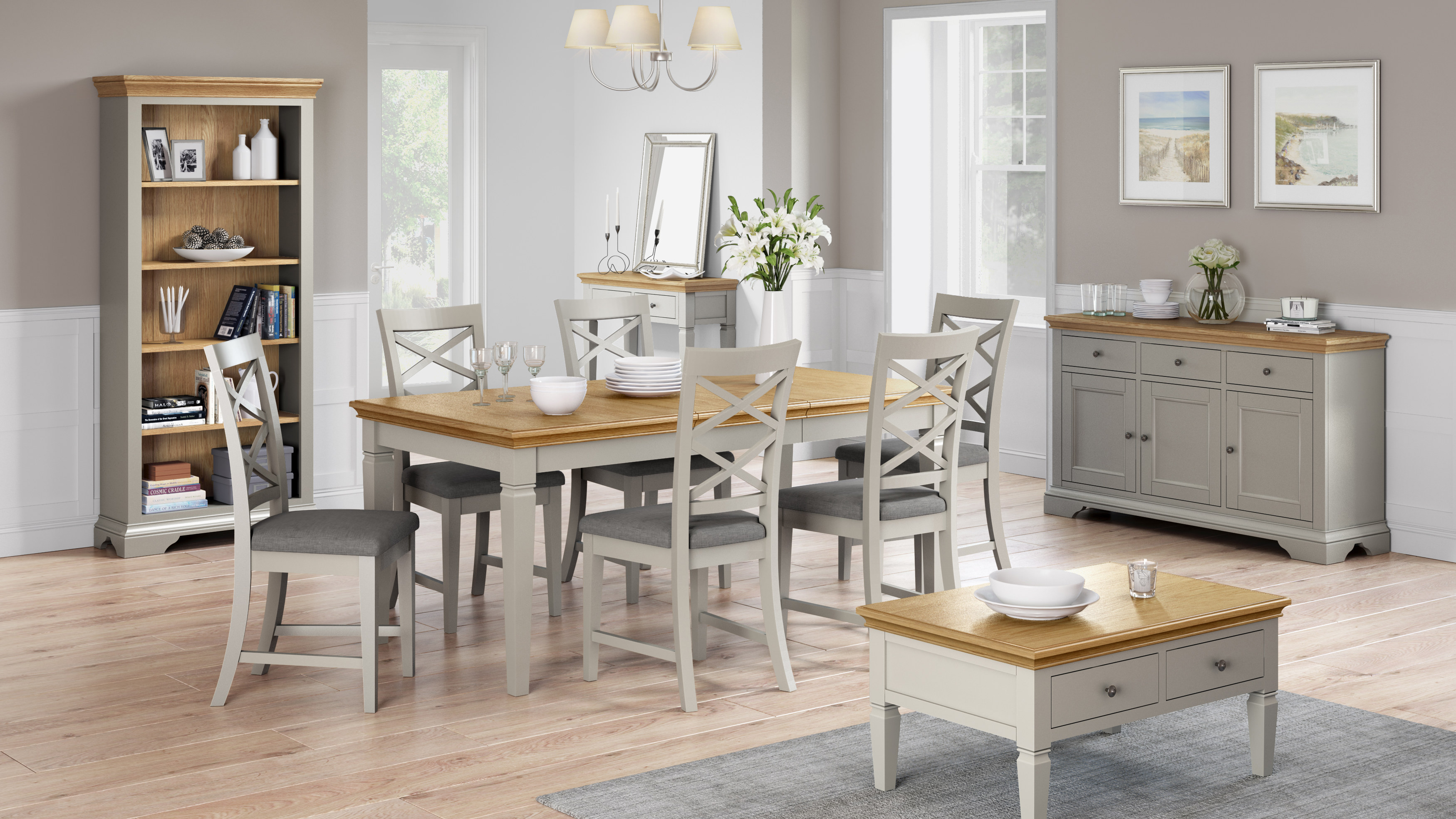 Rustique Home 100% Solid Painted Oak Dining set with table with six chairs. The Chairs are soft grey color with cross backs and the table is grey with natural oak color top. The dining set is complemented by a bookcase, coffee table, a sideboard and a matching console table.
